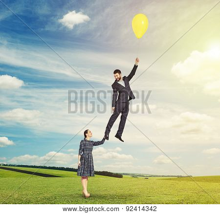 bright outdoors photo of flying man with yellow balloon