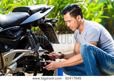 Asian man doing motorcycle maintenance in his garden
