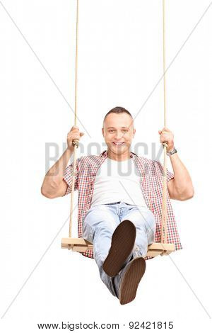 Vertical shot of a carefree young man swinging on a wooden swing and looking at the camera isolated on white background