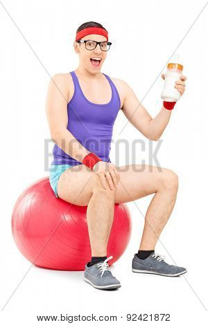 Vertical shot of a nerdy guy in sportswear sitting on a fitness ball and holding a huge baby bottle full of milk isolated on white background