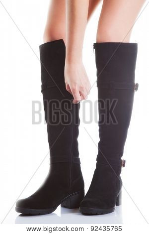 Beautiful female legs in black suede boots on a white background. hand buttons zipper