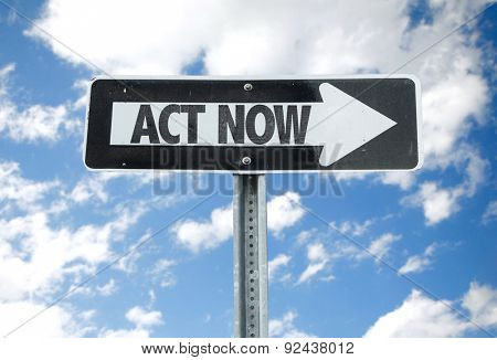 Act Now direction sign with sky background
