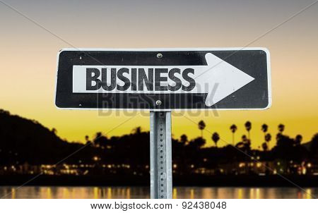 Business direction sign with sunset background
