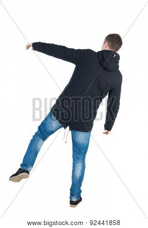 Balancing young man or dodge falling man. Rear view people collection.  backside view of person.  Isolated over white background. A guy in a black jacket with a hood on his right leg wobbles.