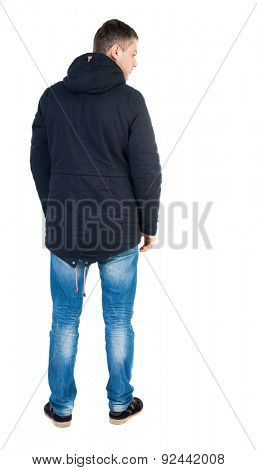 Back view of handsome man in winter jacket  looking up. Standing young guy in parka. Rear view people collection.    Isolated over white background. A guy in black jacket with a hood looks down sadly.