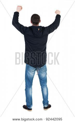 Back view of  man.  Raised his fist up in victory sign.   Rear view people collection.  backside view of person.   A guy in a black jacket with a hood over his head with his fists waving