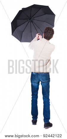 Back view of man in jeans under an umbrella. Standing young guy. Rear view people collection.  backside view of person.  Isolated over white background. guy is trying to keep wind break-out umbrella