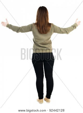 back view dancing young beautiful woman. girl watching. Rear view people collection.  backside view person. Isolated over white background. girl in gray sweater is widely spreading his hands to sides.