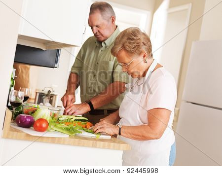 elderly senior couple at home preparing vegetables for a meal