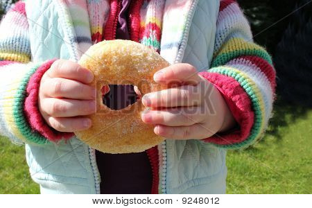 Child Holding A Ring Doughnut