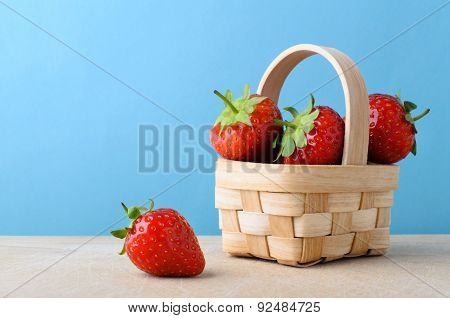 Strawberries In Small Basket With Blue Background
