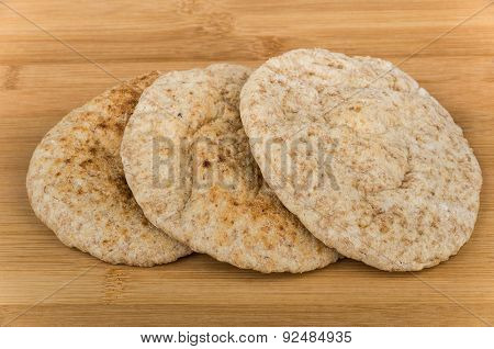 Three Small Pitas On Wooden Board