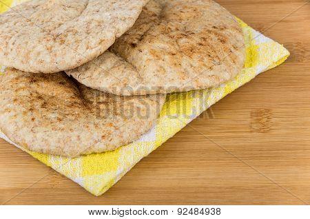 Three Small Pitas On Yellow Napkin