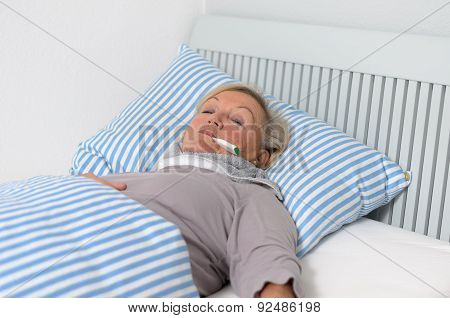 Sick Woman Lying On Bed With Thermometer In Mouth