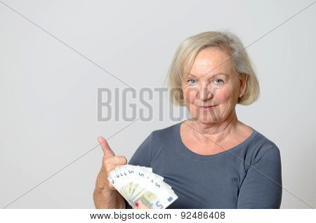 Senior Woman Holding Fan Of Euros With Thumbs Up