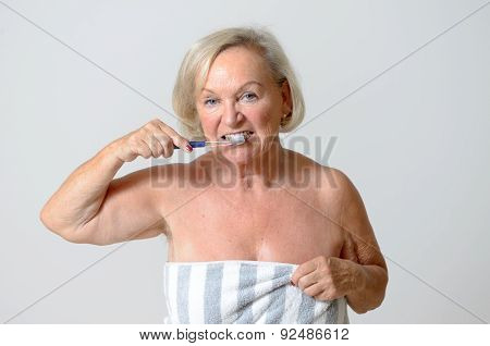 Senior Woman Wrapped In Towel Brushing Her Teeth
