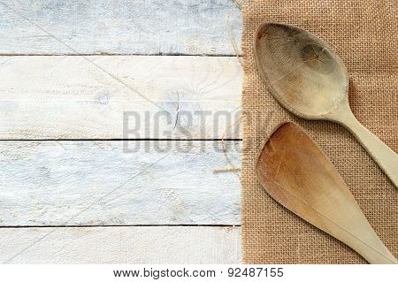 Wooden dipper kitchenware on a sackcloth on a white wooden table