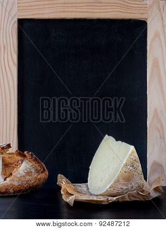 Soft Cheese Wedge In Front Of Blank Old Blackboard Carte.