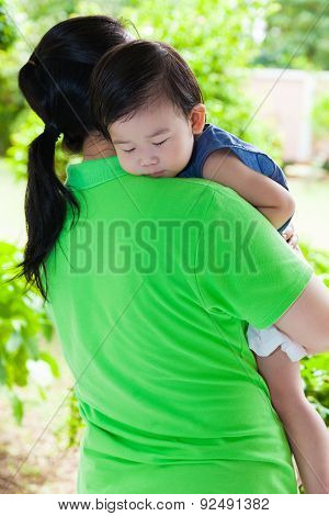 Mother Carrying Her Daughter In Home Backyard