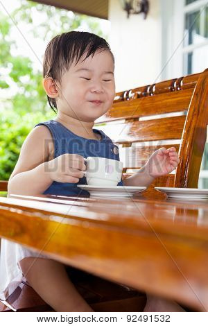 Little Asian Girl Smiling And Holding A Teacup