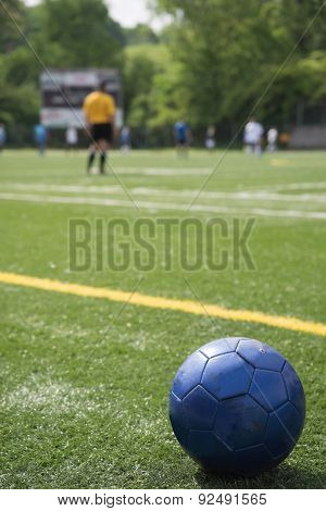 Soccer ball on field with teams, scoreboard, referee in background