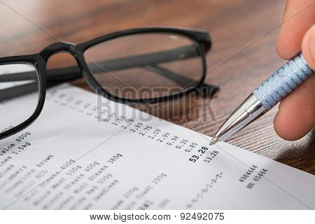 Person Hands With Pen Over Receipt And Eyeglasses