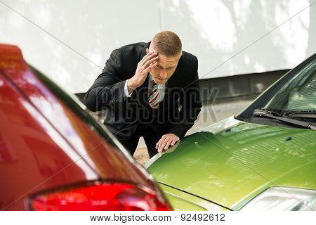 Stressed Driver Looking At Car After Traffic Collision