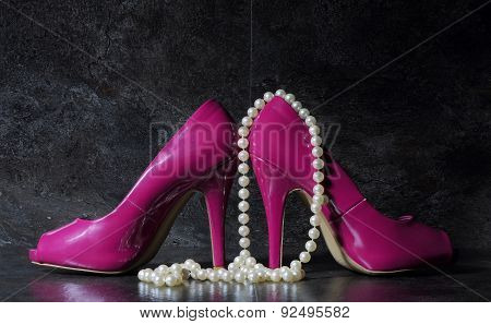 Ladies Pink High Heels With Long Strand Of White Pears Against A Dramatic Black Slate Background Sti