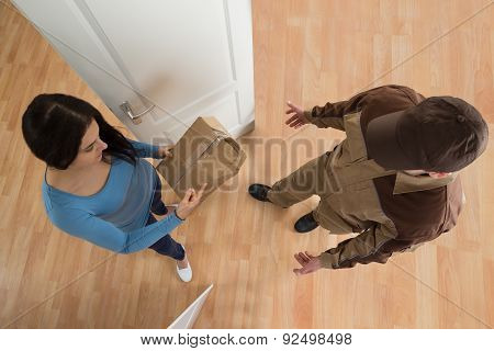 Woman Receiving Damaged Package From Delivery Man