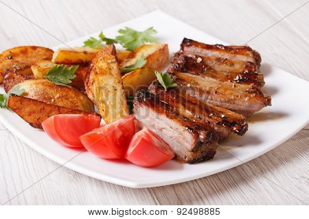 Pork Ribs, Potatoes And Tomatoes On A Plate Close-up
