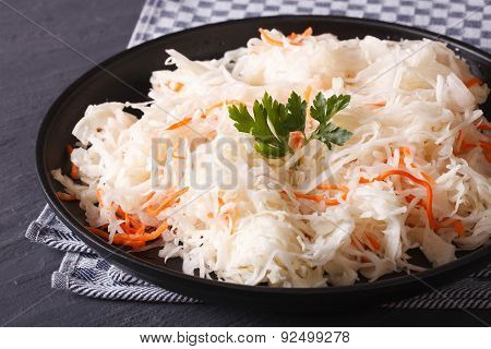 Sauerkraut And Carrots In A Black Plate Close-up Horizontal