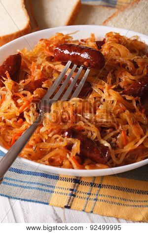 Sauerkraut With Sausages Close-up In White Plate. Vertical
