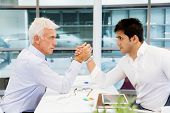 picture of wrestling  - Two businessmen competeting arm wrestling in office - JPG