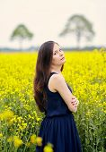 stock photo of cross-dress  - Profile of young beautiful woman with dark blue sleeveless dress and long dark hair standing on yellow blooming rapeseed field with crossed arms - JPG