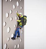 stock photo of climb up  - smiley man in equipment holding on climbing wall and showing thumbs up over white background - JPG