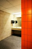 stock photo of mixing faucet  - Public bathroom with light over the sink contrasted by darkness behind the orange tile wall - JPG