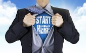 pic of start over  - businessman showing Start here words underneath his shirt over blue sky - JPG