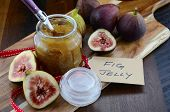 stock photo of jar jelly  - Fresh ripe Autumn fruit figs with fig jelly preserve in jar on cutting board against dark wood background - JPG