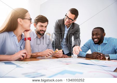 Reach common goal. Positive delighted smiling colleagues sitting at the table and discussing project while working in the office