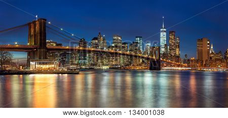 New York - Panoramic view of Manhattan Skyline with skyscrapers  and famous Brooklyn Bridge by night, big size