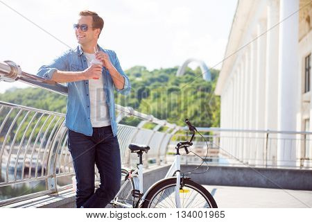 Nice day. Cheerful smiling young man with sunglasses standing and drinking a beverage near a bike