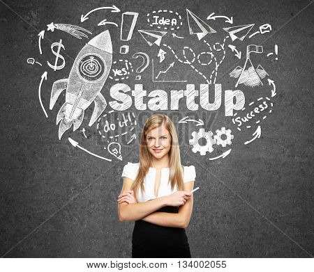 Startup concept with confident young businesswoman and rocket ship sketch on concrete background
