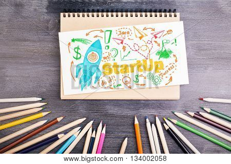 Start up concept with rocket ship sketch on notepad placed on wooden desktop with colorful pencils