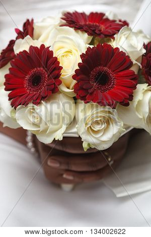 White and red wedding bouquet of roses and gerber flowers in the hands of the bride