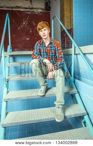 Boy Sitting On The Stairs Of An Old Waterless Pool