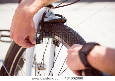 Last checking. Picture of hands of a man checking a wheel of his bicycle before riding