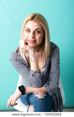 I am waiting for you. Portrait of attractive young woman sitting and looking at camera with anticipation. She is smiling
