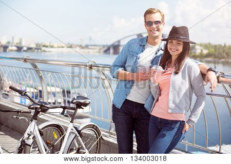 Walking together. Happy young couple having a drink and looking at the camera while standing near a bicycle on the quay