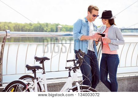 Look here. Handsome smiling guy and pleasant woman with a hat looking at the smartphone while standing near bicycles
