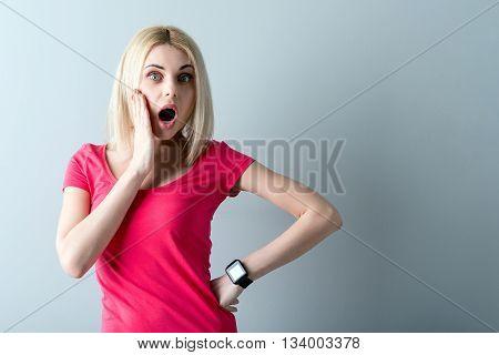 Portrait of attractive young woman opening her mouth with shock. She is standing and raising arm to face. Isolated and copy space in right side